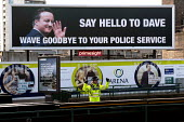 Police officer cheering below West Midlands Police Federation poster Say hello to Dave, wave goodbye to your police service, Conservative Party conference, Birmingham - Timm Sonnenschein - 07-10-2012