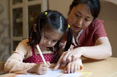 A year one schoolgirl practicing neat writing doing her homework with the help of her mother - Timm Sonnenschein - 2010s,2012,adult,adults,asian,asians,at,BAME,BAMEs,BME,bmes,care,carer,carers,caring,child,childcare,CHILDHOOD,CHILDMINDING,children,chinese,cities,city,diversity,early years,edu,educate,educating,edu