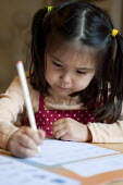 A year one schoolgirl practicing neat writing, doing her homework. - Timm Sonnenschein - 2010s,2012,asian,asians,at,BAME,BAMEs,BME,bmes,child,CHILDHOOD,children,chinese,cities,city,CONCENTRATE,concentrating,concentration,diversity,edu,educate,educating,education,educational,ethnic,ethnici