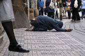 A beggar in the streets of Prague as tourists walk by. - Timm Sonnenschein - 04-06-2012
