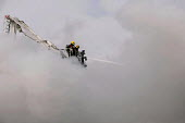 Firefighters spraying a jet of water from a hydraulic platform. West Midlands Firefighters attending a fire that broke out in a Cash Converters shop, suspected arson, Kings Heath, Birmingham - Timm Sonnenschein - 2010s,2013,adult,adults,arson,Birmingham,burn,burning,BURNS,Cash,cities,city,DIA,employee,employees,Employment,fire,Fire and Rescue,fire brigade,firefighter,firefighters,firefighting,fireman,firemen,f