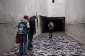 Visitors walking through 10,000 open-mouthed faces cut from circular iron plates. Shalechet (Fallen Leaves), Art in the Memory Void by the artist Menashe Kadishman, Jewish Museum, Berlin, Germany - Timm Sonnenschein - 06-04-2013