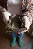 Maggie showing her almost empty purse, in her council flat in Moseley, Birmingham. She is required to pay bedroom tax for one room, which she cant pay, the discretionary payment will not help in the l... - Timm Sonnenschein - 2010s,2013,alone,austerity cuts,bedroom,bedroom tax,BEDROOMS,benefit benefits,Benefit cuts,budget,budgeting,cities,city,claimant claimants,coin,Coinage,coins,cost,council,crisis,debt debts,DOWNTURN,EB