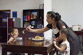 A mother helping her son and nephew with their dinner, De Qing, Moganshan, China - Timm Sonnenschein - &, Chinese,2010s,2013,adult,adults,boy,boys,child,childhood,children,China,dining,dinner,dinners,eat,eaters,eating,families,family,FEMALE,food,FOODS,fussy eater,helping,juvenile,juveniles,kid,kids,lei