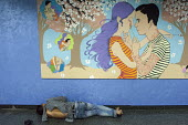 A homeless man sleeping below an artwork by Shannon Toth, a Nippon Paint comissoned illustration - in the name of love Refresh Life, 2013 Metro painted artwork showing a happy couple in love, tube sta... - Timm Sonnenschein - 22-08-2013