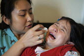 A mother attending to her crying child with a damp tissue after she hurt her jaw. - Timm Sonnenschein - 2010s,2013,accident,accidental,accidents,adult,adults,asian,asians,assisting,CARE,carer,carers,child,Child Care,childcare,CHILDHOOD,CHILDMINDING,children,chinese,cities,city,comforting,cry,crying,damp