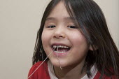A six year old girl preparing for having her milk tooth pulled out by a string tied to a closing door at home. - Timm Sonnenschein - 1st,2010s,2013,asian,asians,BAME,BAMEs,BME,bmes,child,CHILDHOOD,children,chinese,cities,city,closing,dental,dentist,dentistry,dentists,diversity,DIY,do it yourself,door,doors,ethnic,ethnicity,female,f