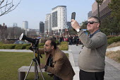 People using adapted camera and phone to view a partial solar eclipse as the moon passes infront of the sun, Birmingham. - Timm Sonnenschein - 2010s,2015,amateur,Amateur Photographer,cities,city,eni,environment,Environmental Issues,hobbies,hobby,hobbyist,Leisure,LFL,LIFE,moon,nature,PEOPLE,photograph,photographers,photographs,photography,REC