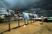 A refugee woman hanging her washing on a wire fence as storm clouds aproach .Kibuye refugee camp, Rwanda, 2003 - Steven Langdon - 01-03-2003