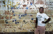 Rwandan boy standing with a wall showing a map of petrol stations, Kigali, Rwanda, 2003 - Steven Langdon - 01-03-2003