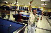 A young man from Iraq whose family are seeking asylum in Holland playing pool at an asylum reception centre, Dronten. Netherlands, 2005 - Steven Langdon - 2000s,2005,Asylum Seekers,Asylum Seekers,BME minority ethnic,Diaspora,displaced,dutch,eu,europe,european,europeans,eurozone,families,family,foreign,foreigner,foreigners,holland,housing,immigrant,IMMIG