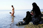 Two Jordanian women look on as western tourists enter the water on the East bank of the Dead Sea. Jordan, 2004 - Steven Langdon - 2000s,2004,bank,BANKS,bather,bathers,bathing,beach,BEACHES,bodies,body,COAST,coastal,coasts,Dead,developing,dress,EBF Economy,EXERCISE,FEMALE,hajib,headscarf,hijab,holiday,holiday maker,holiday makers