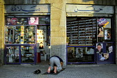 A Jordanian man prays in front of his video store on King Talal Street in the downtown area of the capital, Amman. Jordan,2004 - Steven Langdon - 2000s,2004,Belief,bought,buy,buyer,buyers,buying,capital,commodities,commodity,consumer,consumers,customer,customers,developing world,EBF Economy,goods,islam,ISLAMIC,jordan,Jordanian,Jordanians,man me