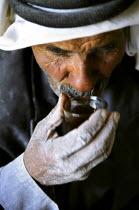 A Bedouin man sips a glass of tea during a break from flour making in Wadi Musa near Petra. Jordan, 2004 - Steven Langdon - 2000s,2004,age,ageing population,arab,arabic,arabs,break,break time,developing,drink,drinker,drinkers,drinking,elderly,employee,employees,Employment,flour,food,FOODS,job,jobs,jordan,Jordanian,Jordania
