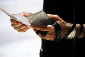An Orthodox Jewish man reads extracts from the Tenach and his arm wrapped in a tefillah during prayer at the wailing wall also known as the wailing wall - in the Old City. Jerusalem, Israel, 2005 - Steven Langdon - 28-10-2005