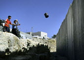 Palestinian children throw rubbish at the Israeli security wall near their homes in the Abu Dis area of East Jerusalem. The West Bank, 2005 - Steven Langdon - 30-10-2005