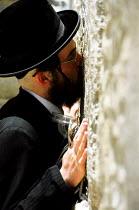 Orthodox Jews praying at the western wall - also known as the wailing wall - in the Old City. Jerusalem, Israel, 2005 - Steven Langdon - 2000s,2005,Al-Haram,al-Qudsi,al-Sharif,Har ha-Bayit,Hasidic,Hasidism,holiest site,holy site,in,israel,israeli,Israelis,Jerusalem,jew,jewish,jews,judaism,kiss,kissing,Kotel,male,man,men,middle east,mon