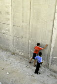 Two Palestinian boys draw Israeli and Palestinian flags with chalk near their homes which are next to the Israeli security wall in the Abu Dis area of East Jerusalem. The West Bank, 2005 - Steven Langdon - 30-10-2005