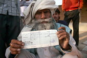 An elderly farmer from the district of Mawranipur with a cheque for 400 rupees intended to assist him in the drought. Like many farmers he doesnt have a bank account and has no idea how is he to get i... - Tashi Tobgyal - 31-01-2008