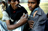 Bangladeshi drug users injecting one another with a synthetically produced opiate called Bupererorphine. This drug is supplied to the drug users, along with clean needles and syringes as part of a pro... - Thomas Morley - 2000s,2002,Acquired immune,addict,addiction,addicts,against,AIDS,arm,asia,asian,asians,Bangladesh,Bangladeshi,Bangladeshis,buprenorphine,cities,city,CLJ,deficiency syndrome,developing,drug,drug users,