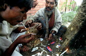 Bangladeshi men smoking heroin in a park in Dhaka. The drug is brown sugar a very impure and dangerous form of heroin. It is often mixed with bathroom cleaning powders and coupled with the fact that i... - Thomas Morley - 12-03-2002