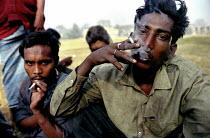 Bangladeshi men smoking cigarettes after injecting heroin in a park in Dhaka, Bangladesh 2002 - Thomas Morley - 12-03-2002