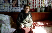 An Abkhazian woman, a refugee on her bed in front of a wall decorated with cigarette packets and pictures from magazines in the single room she shares with her daughter and her children in an old cond... - Thomas Morley - ,2000s,2003,Abkhaz,Abkhazian,Abkhazians,Abkhazs,age,ageing population,asia,asian,asians,BAME,BAMEs,BME,bmes,building,BUILDINGS,caucasus,central asia,CHILD,CHILDHOOD,children,Civil War,communities,comm