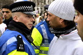 Policeman talking to Muslim youth. United Rally against Islamaphobia after publication of cartoon caicatures of the Islamic prophet Muhammed in Denmark and throughout the world. Trafalgar Square Londo... - Kevin Hayes - 11-02-2006