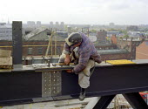 Construction worker bolting steel girders high above Manchester. - Len Grant - 20-02-2002