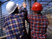 Construction workers installing protective plastic sheeting on a construction site - Len Grant - 03-09-2001