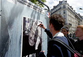 Protesters defacing a FN poster. Paris May Day anti nazi demonstration after the shock result for Jean-Marie Le Pen in the Presidential Election. - Paul Mattsson - 2000s,2002,a,activist,activists,bigotry,CAMPAIGN,campaigner,campaigners,CAMPAIGNING,CAMPAIGNS,defacing,DEMONSTRATING,demonstration,DEMONSTRATIONS,DISCRIMINATION,equal,equality,eu,Europe,european,europ