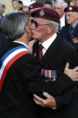 British airborne war veteran kisses and embraces a council official after receiving a commemorative medal from him at local small town D Day sixtieth anniversary commemoration ceremony, Trouarn, Norma... - Paul Mattsson - 06-06-2004