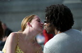 A couple kiss. Summer in Trafalgar Square, London - Paul Mattsson - 2000s,2002,adult,adults,and,BAME,BAMEs,black,BME,bmes,boyfriend,BOYFRIENDS,cities,city,Couple,COUPLES,cultural,diversity,emotion,EMOTIONAL,EMOTIONS,engaged,engagement,ethnic,ethnicity,female,girlfrien