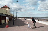 Father, child and ice cream. Spittal promenade, Berwick-upon-Tweed, Northumberland - Paul Mattsson - 2000s,2002,Beach,BEACHES,Berwick-upon-Tweed,Child,CHILDHOOD,CHILDREN,CLOUD,Clouds,COAST,coastal,coasts,DAD,DADDIES,DADDY,DADS,families,FAMILY,Father,FATHERHOOD,FATHERS,holiday,holiday maker,holiday ma