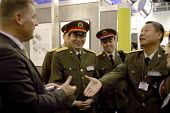 An arms dealer warmly greets a delegation of senior Chinese Army officers. Defence Systems and Equipment International Exhibition, Excel, Docklands - Paul Mattsson - ,2000s,2003,Armaments,Armed Forces,Arms Fair,arms selling,Arms Trade,army,Cap,capitalism,capitalist,Caps,China,Chinese,cities,city,commander,commanders,deal,dealer,Dealers,dealing,defence,defense,Disp