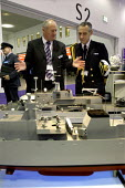 A senior naval officer and an arms dealer discuss the relative sizes of various model warships. Defence Systems and Equipment International Exhibition, Excel, Docklands - Paul Mattsson - ,2000s,2003,Armaments,Armed Forces,Arms Fair,arms selling,Arms Trade,army,boat,boats,Cap,capitalism,capitalist,Caps,cities,city,commander,commanders,dealer,Dealers,dealing,defence,defense,Display,Disp