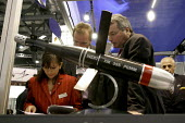 Representatives of Diehl Munitions Systems looking at their corporate paperwork. On display is one of their precision guided mortar rounds. Defence Systems and Equipment International Exhibition, Exce... - Paul Mattsson - 2000s,2003,Armaments,Armed Forces,Arms Fair,arms selling,Arms Trade,army,bomb,bombs,capitalism,capitalist,cities,city,dealer,Dealers,dealing,defence,defense,Display,Displays,DSEI,EBF economy,EXCel,Exh