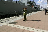 A senior Chinese military officer uses a digital camcorder to film HMS Grafton, a British Royal Navy Duke Class Anti Submarine frigate which is moored at the side of Royal Victoria Dock. Defence Syste... - Paul Mattsson - 2000s,2003,Armaments,Armed Forces,Arms Fair,arms selling,Arms Trade,army,boat,boats,Briefcase,Britain,Cap,capitalism,capitalist,Caps,China,Chinese,cities,city,CLOUD,Clouds,dealer,Dealers,dealing,defen