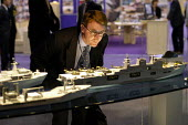 Man in a suit looking at model warships and aircraft carrier. Defence Systems and Equipment International Exhibition, Excel, Docklands - Paul Mattsson - 09-09-2003