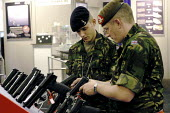 British soldiers trying Heckler and Koch semi automatic pistols. Defence Systems and Equipment International Exhibition, Excel, Docklands - Paul Mattsson - 2000s,2003,Armaments,armed,Armed Forces,arms,Arms Fair,arms selling,Arms Trade,army,Beret,Berets,camouflage,capitalism,capitalist,cities,city,dealer,Dealers,dealing,defence,defense,Display,Displays,DS