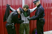 An anti arms trade protester is stopped and searched by Metropolitan Police officers under the draconian Terrorism Act 2000 while protesting outside the Defence Systems and Equipment International Exh... - Paul Mattsson - 10-09-2003