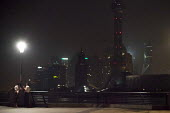 Shanghai, two women talking on riverfront by The Bund, the lights have been switched off to save the cost of electricity. Shanghai, China. - Connor Matheson - 02-09-2015