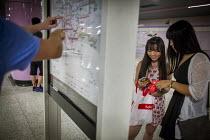 Tourists planning a journey on the subway system. Shanghai, China. - Connor Matheson - Chinese,2010s,2015,adolescence,adolescent,adolescents,china,cities,City,direction,directions,EBF,Economic,Economy,female,females,girl,girls,holiday,holiday maker,holiday makers,holidaymaker,holidaymak