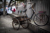 A tricycle chained up in a street, Shanghai, China. - Connor Matheson - 03-09-2015