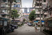A woman walking through housing estate Pudong, Shanghai, China. - Connor Matheson - 05-09-2015
