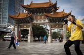 Miming to western pop songs by the Traditional Chinese Gates. Kunming, Yunnan Province, China. - Connor Matheson - 2010s,2015,ACE,architecture,buildings,china,Chinese,cities,City,Culture,Leisure,LFL,LIFE,male,man,melody,men,music,MUSICAL,outdoors,Park,parks,PEOPLE,person,persons,pop,Pop music,RECREATION,RECREATION