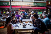 Locals eating food. Kunming, Yunnan Province, China. - Connor Matheson - Chinese,2010s,2015,catering,china,cities,City,eat,eating,FEMALE,food,FOODS,male,man,men,outlet,outlets,people,person,persons,restaurant,restaurants,taste,Urban,woman,women,Young,younger,Youth