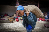 Elderly Bai woman carrying garlic for sale at the local market, Dali, Yunnan Province, China. - Connor Matheson - 18-09-2015