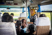 A Uyghur woman, the Chinese muslim minority, collecting fares on the bus. Dali, Yunnan Province, China. - Connor Matheson - 18-09-2015
