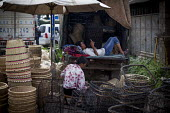 Man resting and woman weaving baskets, busy market, Dali, Yunnan Province, China - Connor Matheson - 18-09-2015